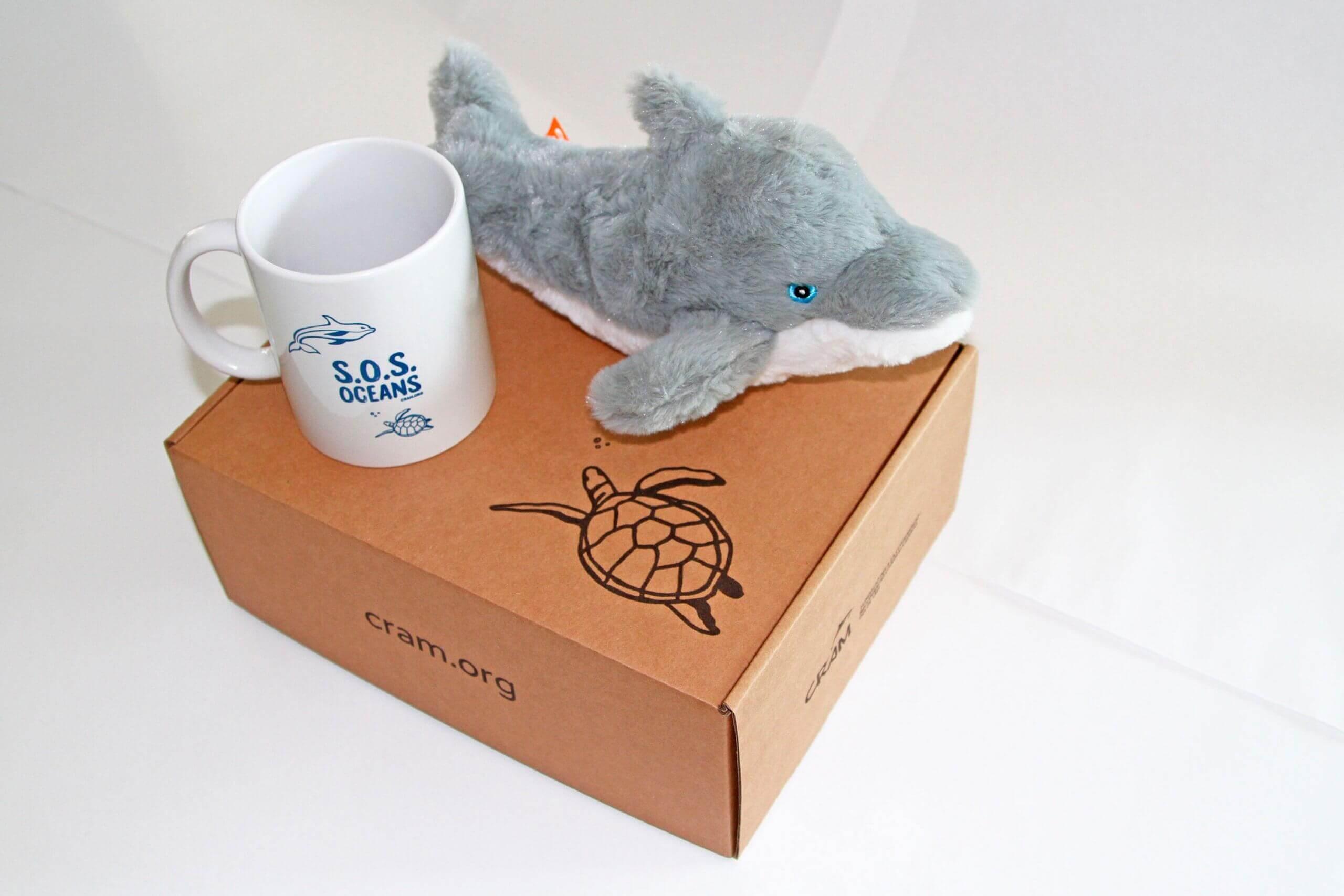 un delfino peluche accanto a una tazza