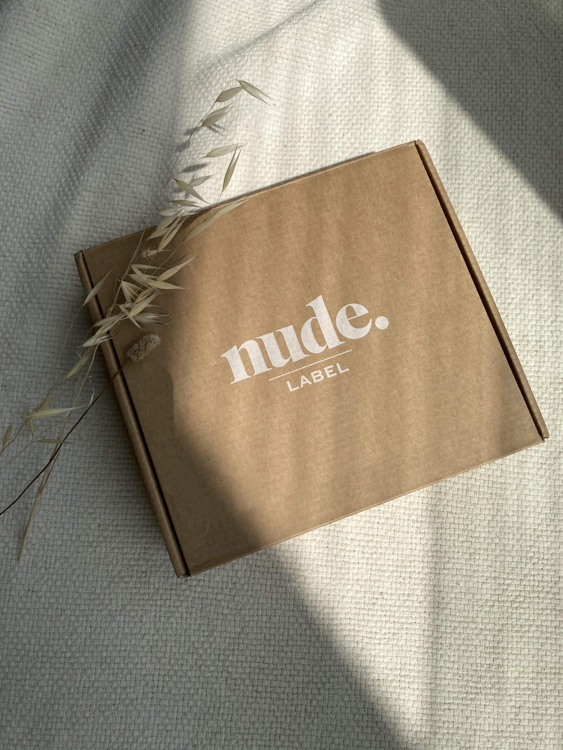 una caja postal con el logo de The Nude Label
