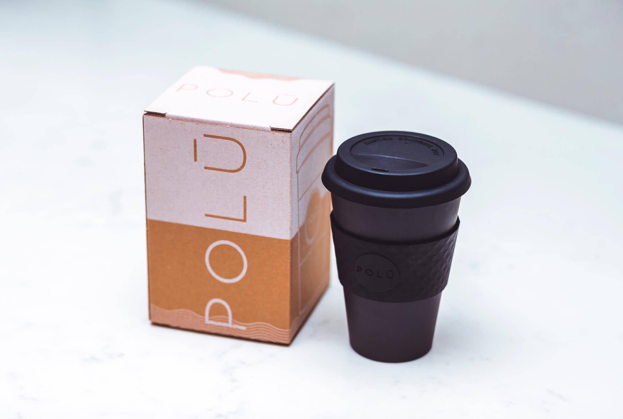 cupă neagră de cafea lângă cutie de produs