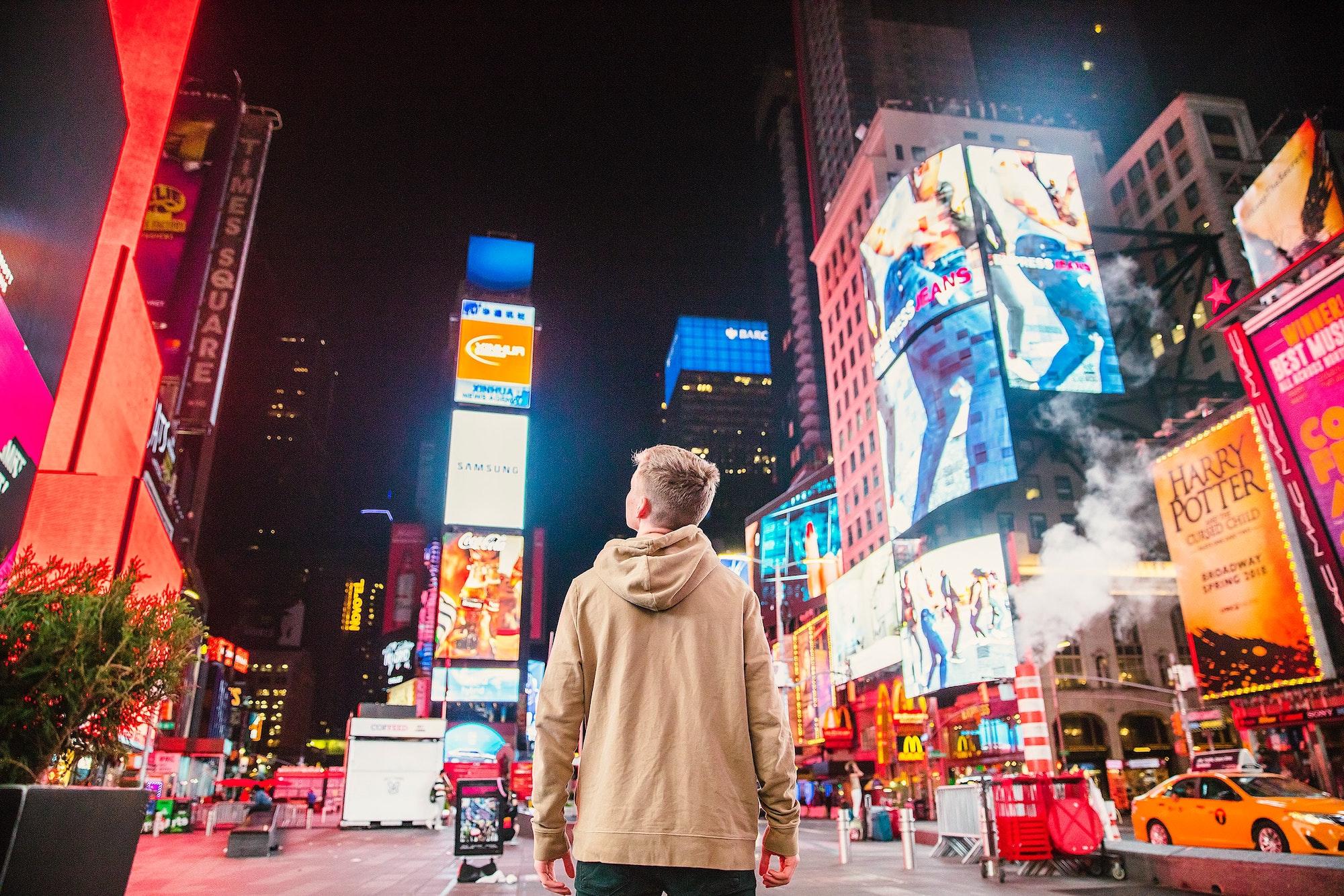Personne face à plein de pubs à Times Square